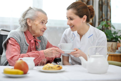 caregiver assisting an elderly with her meal